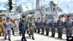 FILE - In this Jan. 8, 2020, file photo released by Indonesian Presidential Office, Indonesian President Joko Widodo, center, inspects troops during his visit at Indonesian Navy ship KRI Usman Harun at Selat Lampa Port, Natuna Islands, Indonesia…