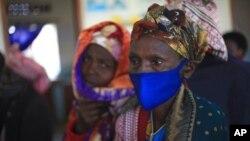 FILE - A woman waits for the AstraZeneca coronavirus vaccine at the Butanda Health Center III in Western Uganda, April 27, 2021.