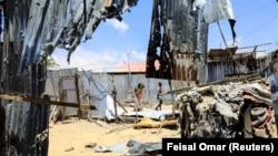 Des civils marchent près de la scène où un tir de mortier a détruit des maisons à l'extérieur d'un complexe tentaculaire qui abrite la base de la Mission de l'Union africaine en Somalie (AMISOM) à l'aéroport de Mogadiscio, en Somalie, le 25 mars 2021.