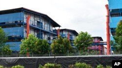In this Sunday, May 10, 2020, photo, people sit outside a building balcony at the S11@Punggol, a complex of dormitory buildings for foreign workers in Singapore. A second wave of coronavirus infections in tightly packed foreign workers' dormitories…