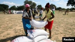FILE - Villagers queue to collect their monthly food aid ration of cereals at a school in drought-hit Masvingo, Zimbabwe, June 2, 2016.