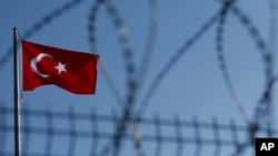 FILE - A Turkish flag is seen fluttering behind a barbed wire fence.