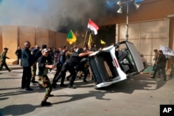 Protesters damage property inside the U.S. embassy compound, in Baghdad, Iraq, Tuesday, Dec 31, 2019.