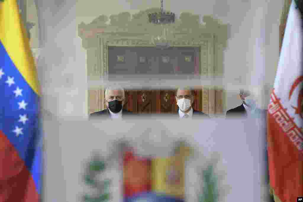 Seen through a translucent podium, Iran's Foreign Minister Mohammad Javad Zarif, left, and Venezuela's Foreign Minister Jorge Arreaza, right, arrive to give a press conference at the Foreign Ministry in Caracas, Venezuela, Thursday, Nov. 5, 2020, amid the