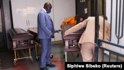 FILE: Undertakers of Sopema Funerals prepare to transport the body of a deceased person ahead of the funeral service, amid a nationwide coronavirus disease (COVID-19) lockdown, in Soweto, south-west of Johannesburg, South Africa August 4, 2020. REUTERS/Siphiwe Sibeko