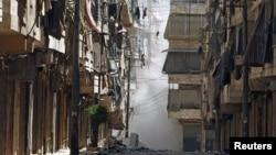 Asap mengepul di antara gedung-gedung di distrik Salah-Edinne, Aleppo, sesaat setelah digempur pasukan pemerintah Suriah (31/7).