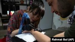 In this Saturday, November 9, 2019, photo, Suraya Shaheedi, 26, Tattoo artist, left, pierced tattoo to a male customer in Kabul, Afghanistan. (AP Photo/Rahmat Gul)
