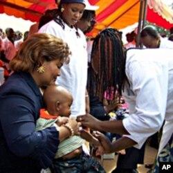 La première dame du Burkina Faso, Chantal Compaoré, aidant à vacciner un enfant contre la méningite en décembre 2010