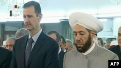 An image grab taken from the state-run Syrian television on August 8, 2013, shows Syrian President Bashar al-Assad (L) and Syrian Grand Mufti Ahmed Hassun attending the morning prayer of Eid al-Fitr in Damascus.