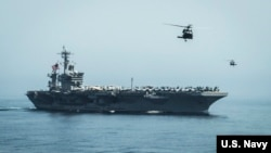 Helicopters fly from the aircraft carrier USS Theodore Roosevelt (CVN 71) during a vertical replenishment with the aircraft carrier USS Carl Vinson (CVN 70), April 13, 2015.