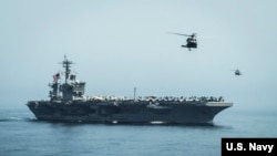 FILE - Helicopters fly from the aircraft carrier USS Theodore Roosevelt in the Gulf of Oman.