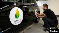 Gambar tempel Konferensi Perubahan Iklim COP21 di Paris pada mobil listrik Nissan LEAF di Boulogne-Billancourt, dekat Paris (16/11). (Reuters/Benoit Tessier)