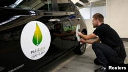 FILE - An employee installs a sticker which reads 100% electric next to the logo of the upcoming COP21 Climate Change Conference on a Nissan LEAF electric car in Boulogne-Billancourt, near Paris, France.