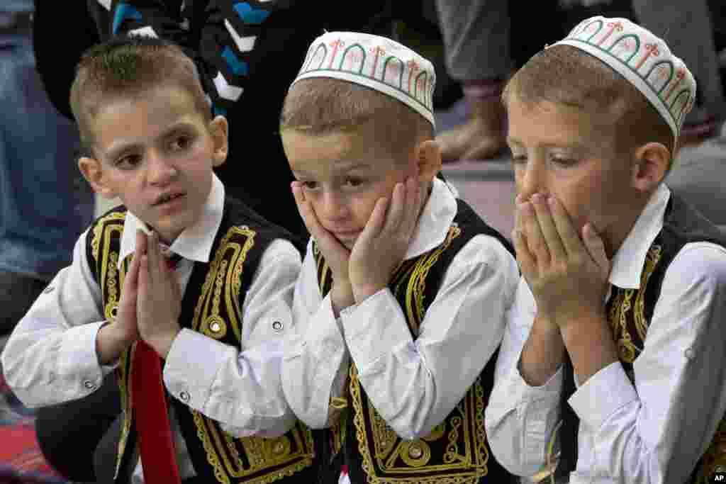ក្មេងៗធ្វើការបួងសួងនៅអំឡុងពេលពិធីបុណ្យ Eid al-Adha ខាងក្រៅវិហារ Sultan Mehmet Fatih ក្នុងក្រុងព្រីស្ទីនណា ប្រទេសកូសូវ៉ូ។