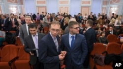 FILE - Jehovah's Witnesses wait in a courtroom in Moscow, Russia, April 20, 2017. On Monday, Russia's Supreme Court has banned the religious group from operating in the country.