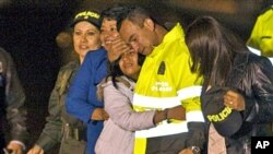 Former hostage Carlos Alberto Ocampo, second right, is reunited with family members upon his arrival to a military airport in Bogota, Colombia after his release by the Revolutionary Armed Forces of Colombia, FARC, February 13, 2011