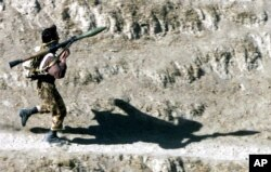 FILE - A fighter armed with a Soviet-made RPG-7 rocket launcher runs towards his position in Northern Afghanistan, Oct. 14, 2001. A U.S. company is selling a redesigned and updated version of the Soviet RPG-7 anti-tank weapon to Ukraine.