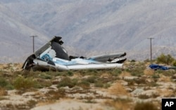FILE - Wreckage lies near the site where a Virgin Galactic space tourism rocket, SpaceShipTwo, exploded and crashed in Mojave, Calif., Oct. 31, 2014.