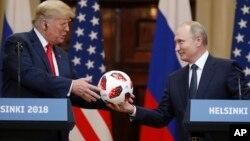 Rossiya Prezidenti Vladimir Putin (o'ngda) Futbol bo'yicha jahon chempionati to'pini AQSh rahbari Donald Trampga sovg'a qilmoqda, Xelsinki, Finlyandiya, 16-iyul, 2018-yil.