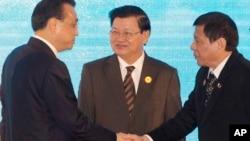 지난해 9월 라오스 수도 비엔티안에서 열린 열린 중국-아세안 정상회의에서 리커창 중국 총리(왼쪽)와 로드리고 두테르테 필리핀 대통령가 악수하고 있다. 통룬 시술릿 라오스 총리가 이를 지켜보고 있다.