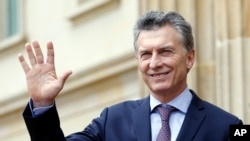 FILE - Argentina's President Mauricio Macri waves at journalists at the end of a welcoming ceremony at the Presidential Palace in Bogota, Colombia, June 15, 2016.