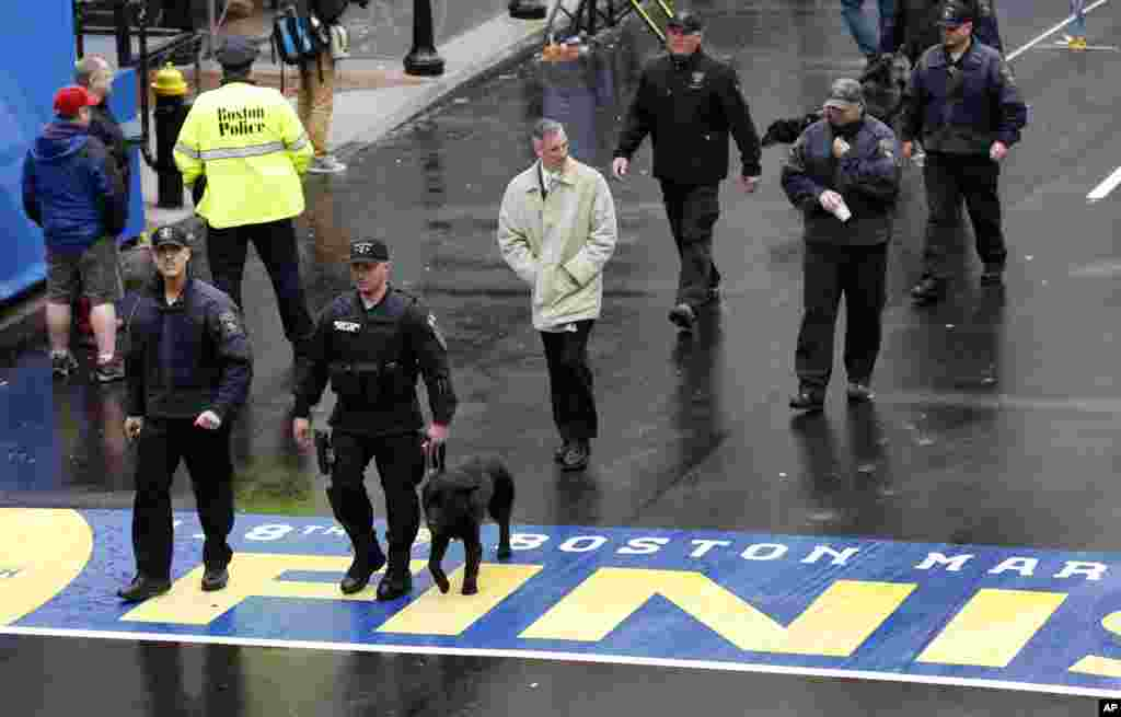 Security personnel walk across the Boston Marathon finish line prior to a remembrance ceremony for family members and survivors of the 2013 Boston Marathon bombing, on Boylston Street, April 15, 2014.