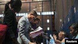 Những người tìm việc nói chuyện với các nhân viên tuyển dụng tại một hội chợ việc làm ở New York