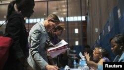 Những người tìm việc làm nói chuyện với các nhân viên tuyển dụng tại một hội chợ việc làm ở New York