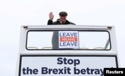 """FILE - Brexit campaigner Nigel Farage gestures during a """"Brexit Betrayal"""" march from Sunderland to London, in Sunderland, Britain, March 16, 2019."""