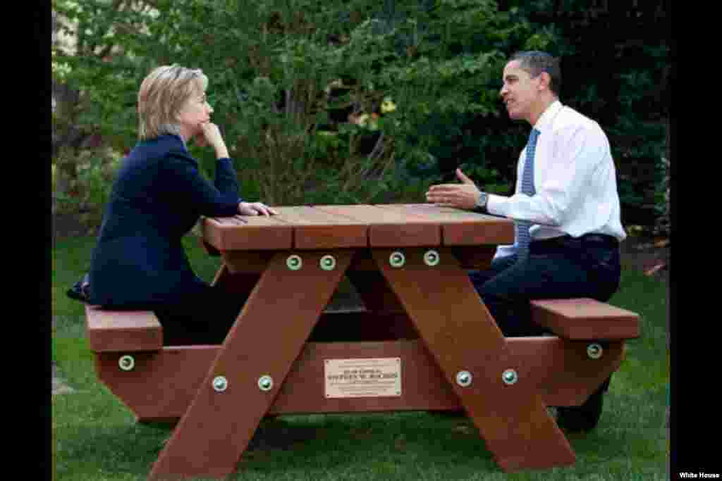 President Barack Obama and Secretary of State Hillary Rodham Clinton speak together sitting at a picnic table, on the South Lawn of the White House, May 9, 2009. ( White House/Pete Souza)