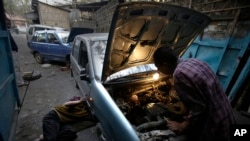 FILE - Indian mechanics repair a small car at a garage in Gauhati, India.