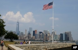 FILE - Tourists view the New York City skyline from Ellis Island, July 29, 2015, in New York. The island, situated in New York harbor, served as an entry point for immigrants to the U.S. from 1892 through 1954.