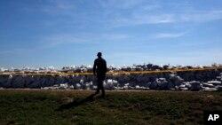 Policajac obilazi vreće peske postavljene na obali Save, u Sremskoj Mitrovici, 22. maja 2014.