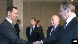شامی صدر بشار الاسد (بائیں) روسی وزیرِ خارجہ سے ہاتھ ملاتے ہوئے