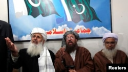 Maulana Sami ul-Haq (C), one of the Taliban negotiators, answers a question during a news conference with his team members Ibrahim Khan (L) and Maulana Abdul Aziz (R) in Islamabad February 4, 2014.