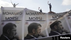 Supporters of President Mohamed Morsi carry a banner with his pictures during a protest to counter anti-Morsi protests elsewhere in Alexandria, July 2, 2013.