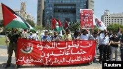 Para pemuda Persatuan Demokrasi Palestina membawa spanduk dan bendera Palestina dan berunjuk rasa di depan markas besar PBB di Beirut menandai peringatan 64 tahun 'Nakba', hijrahnya warga Palestina sejak berdirinya Israel tahun 1948 (15/5).