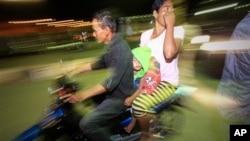 Warga yang panik menjauh dari rumah dengan mengendarai sepeda motor saat gempa kuat menimpa Aceh pada Januari 2013. (Foto: Dok)