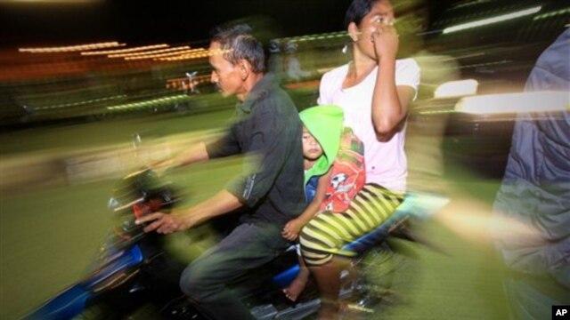Warga yang panik karena gempa di Aceh Selasa (22/1) meninggalkan rumah dengan sepeda motor. (AP/Heri Juanda)