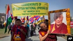 Un monje tibetano carga el retrato de su lider espiritual, el Dalai Lama, a quien el gobierno chino acusa de incitar las inmolaciones.