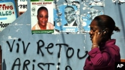 A Haitian woman uses her mobile phone next to a poster of Haiti's presidential candidates Mirlande Manigat in Port-au-Prince, March 18, 2011