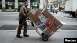 FILE - UPS delivery man pushes a trolley of packages in New York, Dec. 27, 2013.