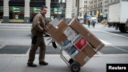 UPS快递公司的人在纽约推着一车包裹