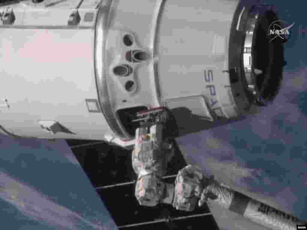 Tangan robotik Stasiun Antariksa Internasional, yang dioperasikan komandan Butch Wilmore, mencapai pesawat SpaceX Dragon saat terbang lebih dari 420 kilometer di atas Laut Mediterania (12/1).