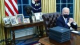 Biden family photos are displayed around a bust of activist Cesar Chavez, as U.S. President Joe Biden prepares to sign executive orders at the Resolute Desk inside the Oval Office of the White House in Washington, U.S., January 20, 2021. Picture taken Jan