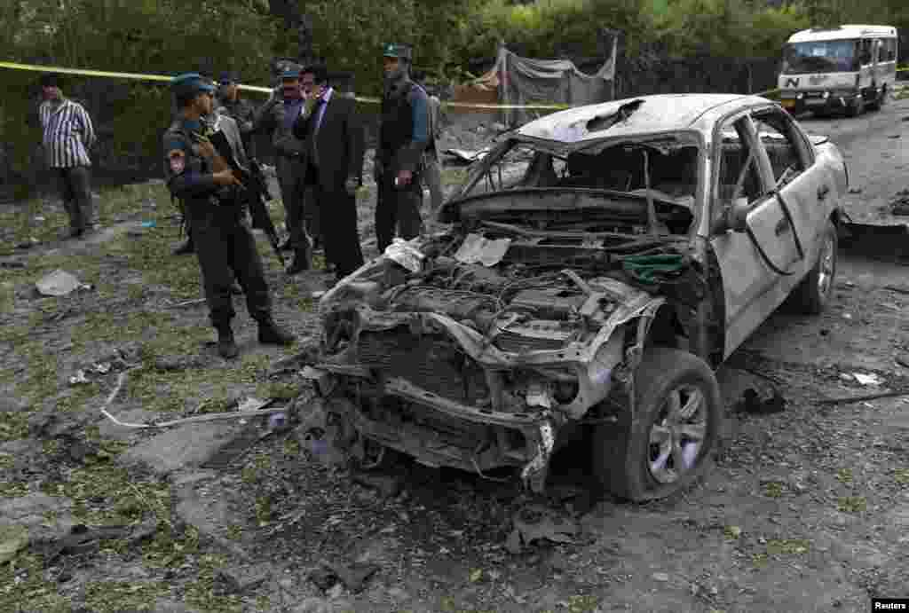 Afghan police inspect at the site of a suicide car bomb attack in Kabul, June 11, 2013.