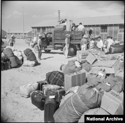 Baggage and luggage of Japanese-American internees newly arrived at the Minidoka camp from western Washington awaits delivery to their barracks in August 1942. (Francis Stewart, War Relocation Authority via National Archives)