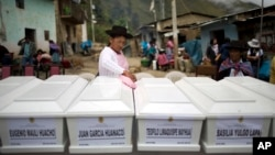 In this March 29, 2016 photo, a woman dusts coffins holding the remains of villagers who were slain more than two decades ago by Shining Path rebels, before a group burial service in Ccano, a village in the Huanta area of Ayachcuo department, Peru. In Ccano, many peasants worked with the military to fight the rebels, and the Shining Path stormed a church here in retaliation, killing everyone praying inside in 1991.