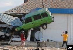 Čovek fotografiše kamionet podignut uvis, nakon razornog zemljotresa i cunamija na plaži u Paluu 1. oktobra 2018.