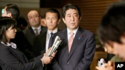 Japan's Prime Minister Shinzo Abe, center, speaks to reporters about the hostage crisis in Tokyo, Jan. 21, 2015. (AP Photo/Shizuo Kambayashi)